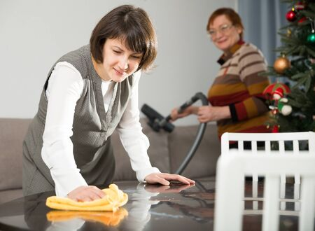 Attractive woman wiping table surface while her elderly mother vacuum cleaning sofa in preparation for celebration of New Year