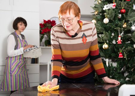 Mature mother with adult daughter tidying up the room before Christmas