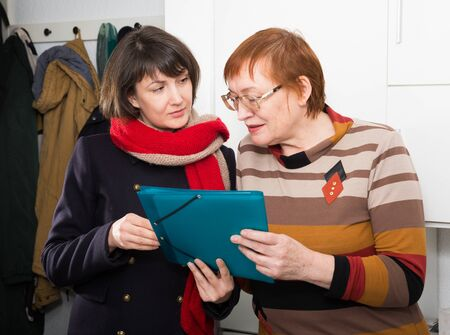 Girl volunteer offers an older woman to read the document