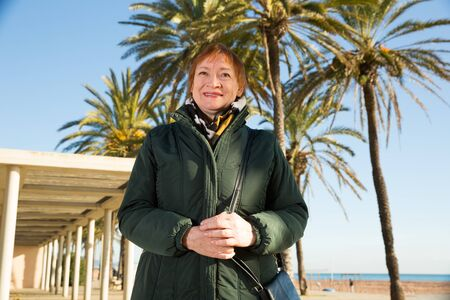 Portrait of attractive smiling middle-aged woman on background of palms on city waterfront in sunny autumn day