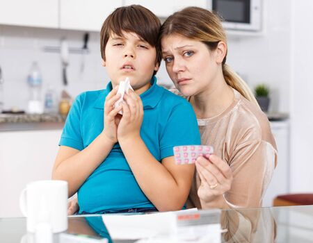 Sick boy sneezing in handkerchief, anxious woman with medicines sitting at kitchen
