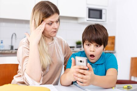 Tweenage boy sitting at kitchen using phone while mom scolding him Stock Photo