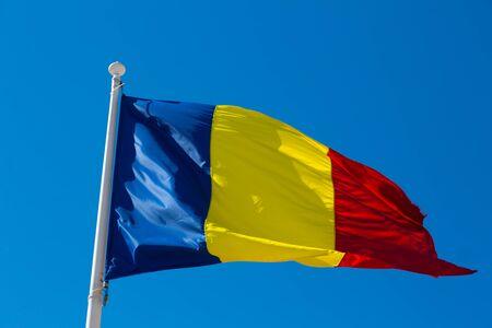 Romanian flag on flagpole waving against blue sky