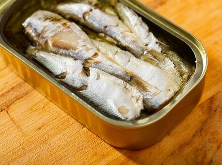 Closeup view of opened can of sardines in oil on wooden table