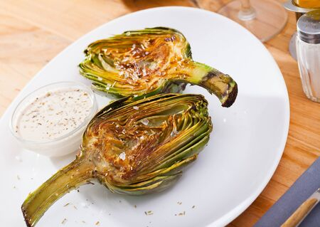 Vegetarian appetizer of roasted halved artichoke served with kosher salt and savory dip sauce
