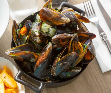 Fresh bivalve mussels served with onion sauce in bowl