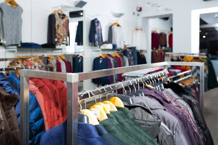 Interior of clothing shop with coats and blouses on hangers and shelfs