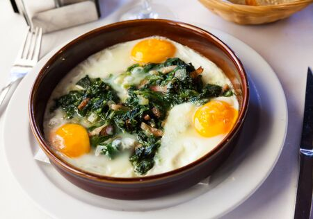 Popular Catalan dish of fried eggs, spinach, raisins and ham served in traditional clay cazuela