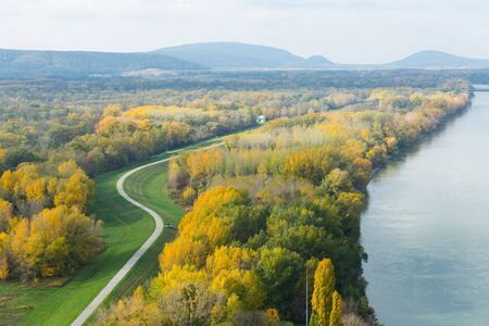 Aerial view of autumn landscape with river and curving road
