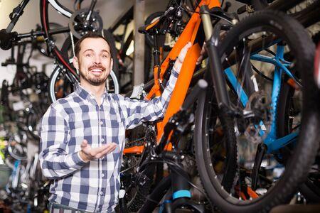 glücklicher spanischer mann in sportwerkstatt montiert fahrrad mit spezialwerkzeugen