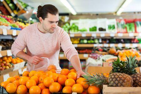 Cliente del giovane che sceglie le arance fresche sul supermercato