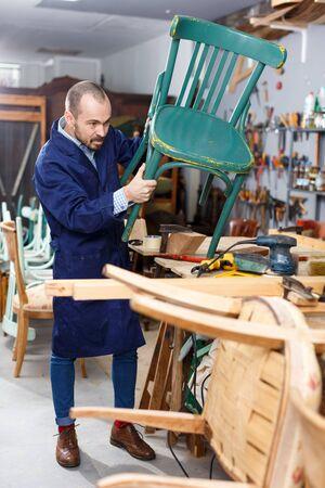 Professional young man carpenter repairing antique furniture in workshop