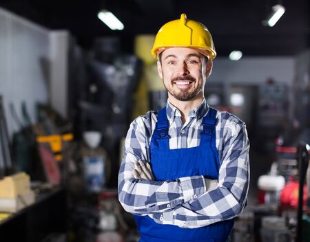 Smiling american  working man demonstrating his workplace and tools at workshop