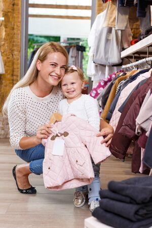 Mujer joven alegre y su pequeña hija de compras en la tienda de ropa para niños