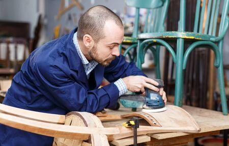 Professional furniture restorer in process of renovation vintage armchair in workshop