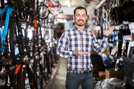 Young cheerful man points to interesting details of bicycle in bike shop
