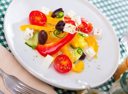 Traditionele Griekse salade met verse groenten, fetakaas en zwarte olijven geserveerd op wit bord Stockfoto