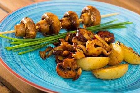 Tasty mix of roasted mushrooms with baked potatoes decorated with chives Фото со стока