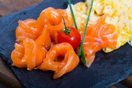Omelet with salmon garnished with fresh scallion and cherry tomato on black serving board Reklamní fotografie