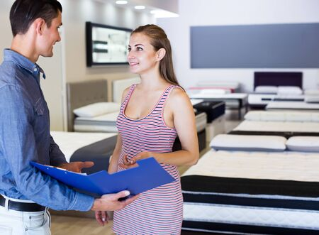 Successful seller offering mattress to female buyer in furniture store Stok Fotoğraf - 130649319
