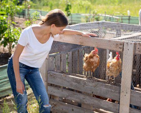 Boerenvrouw voert kippen in een kippenhok Stockfoto