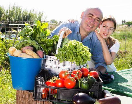 Happy couple with harvest of vegetables in the garden Banco de Imagens