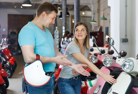 pair are shopping and choosing new motobike in moto store.