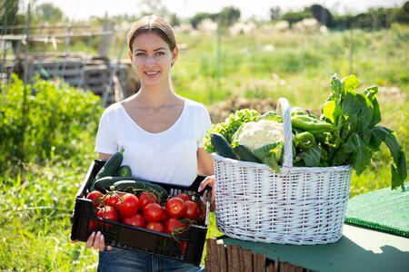 Portrait of young woman gardener with harvest of vegetables and greens in basket in  garden Banco de Imagens