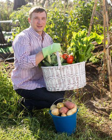 Young man gardener holding basket with harvest of vegetables in garden outdoor
