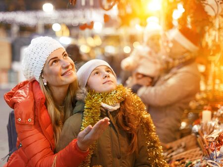 Smiling woman and her nice teenage daughter spending time at Christmas market Banco de Imagens
