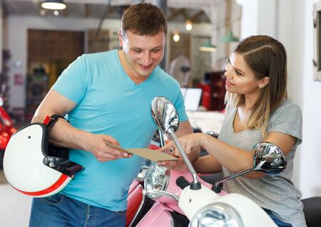 Male with female with flyers choosing new motobike in moto store.
