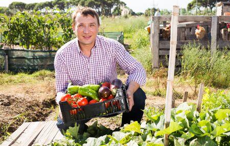Man gardener holding basket with harvest of vegetables, near chicken house in garden outdoor