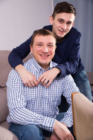 Portrait of guy with his father who are resting together at the home.