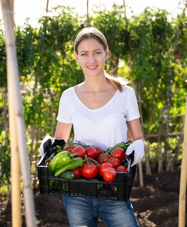Girl farmer with box of vegetables in the garden