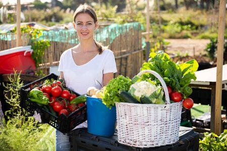 Young woman gardener holding basket with harvest of vegetables in garden outdoor Banco de Imagens