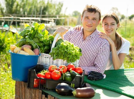 Portrait of young family couple with harvest of vegetables in garden outdoor