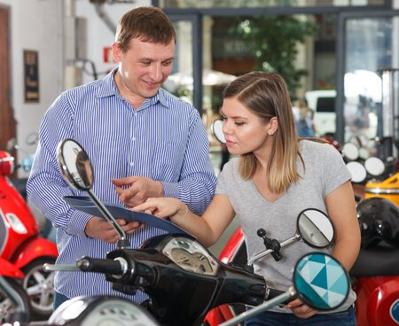 Male with female are talking about new motobikes in the moto store. Фото со стока