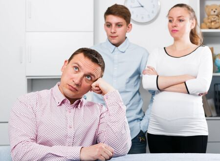 Middle-aged pregnant wife and boy quarrelling with her husband at home