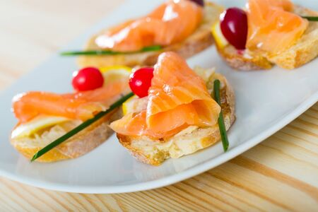 Image of exquisitely served tasty bruschettes with salmon, butter and cranberries