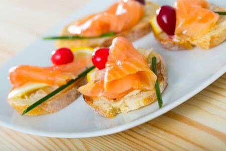Immagine di gustose bruschette squisitamente servite con salmone, burro e mirtilli rossi