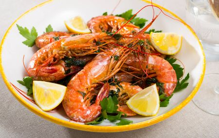 Seafood appetizers, roasted prawns served with parsley and lemon slices