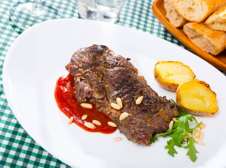 Prepared beef steak with tomatoe ketchup and pine nuts at plate