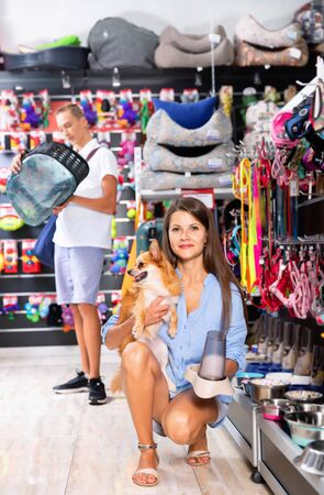 Happy positive smiling young woman with dog in pet store during shopping with man Archivio Fotografico - 130708692