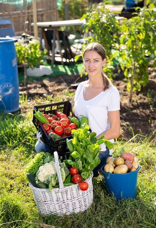Girl farmer with basket and box of vegetables in the garden