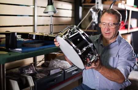 Senior male music master is repairing drums in his workshop