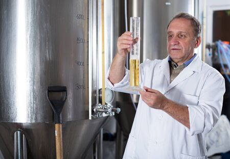 Adult expert is standing with flask for beer and analizying it in the fabric.