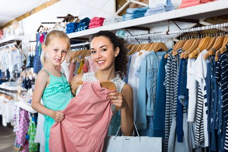 Young woman with small girl choosing pink dress in kids apparel boutique Stockfoto