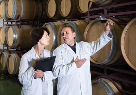 happy worker of winery holds glass of red wine in hand and shows him to expert Stockfoto