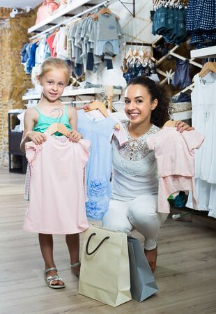 Positive woman with smiling girl choosing clothes in kids apparel boutique Stockfoto - 130775131