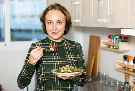 Portrait of young woman standing with plate of salad at home kitchen